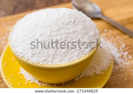 Cup of sorbitol, a natural sweetener on the table next to a spoon. Closeup