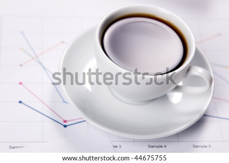 Cup of strong coffee over business diagrams, closeup soft focus photo