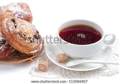 Cup of tea and buns with raisins on white background