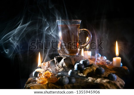 cup of tea and candles. Hot tea with berries and steam  #1355945906