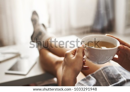 Cup of tea and chill. Woman lying on couch, holding legs on coffee table, drinking hot coffee and enjoying morning, being in dreamy and relaxed mood. Girl in oversized shirt takes break at home