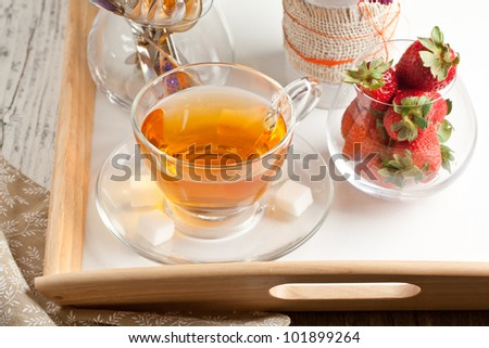 Cup of tea and fresh strawberries served on white tray