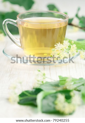 Cup of tea and linden flowers on wooden background
