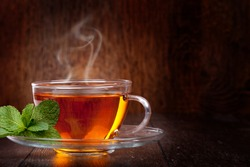Cup of tea and mint on a wooden background