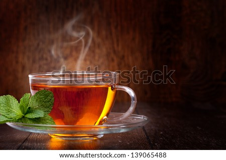 Cup of tea and mint on a wooden background #139065488