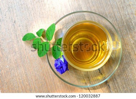 Cup of tea and purple flower on wood background.