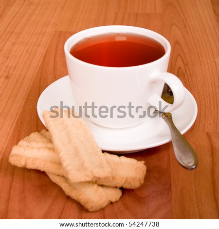 cup of tea and some cookies on wooden table