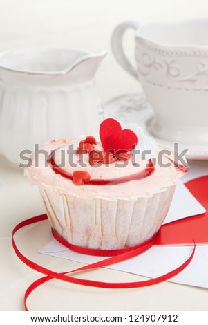 Cup of tea and strawberry cupcake served on a table