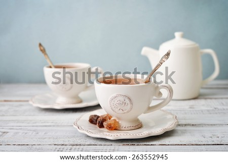 Shutterstock Cup of tea and sugar with teapot over blue background