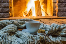 Cup of tea and sugar,  wool scarf near  cozy fireplace, in country house, winter vacation or christmas evening.