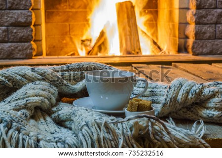 Cup of tea and sugar,  woolen things near  cozy fireplace, in country house, winter vacation, horizontal. #735232516