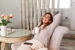 Cup of tea, coffee and chill. Woman lying on couch drinking hot coffee and enjoying morning, being in dreamy and relaxed mood. Girl covered in blanket takes break at home