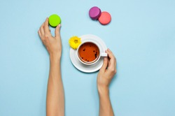 Cup of tea in female hands, colorful sweet cakes macaroons and yellow chrysanthemum on blue background. Delicious breakfast, Concept Good morning, still life with tea cup, postcard. Top view Flat lay
