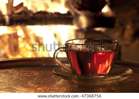 cup of tea in his hands against the backdrop of fire in the fireplace