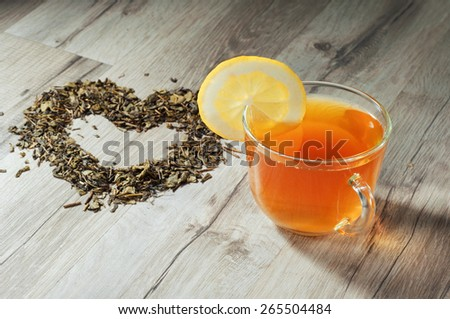 Cup of tea on a wooden table. Next to a cup of tea, heart made of dried tea leaves