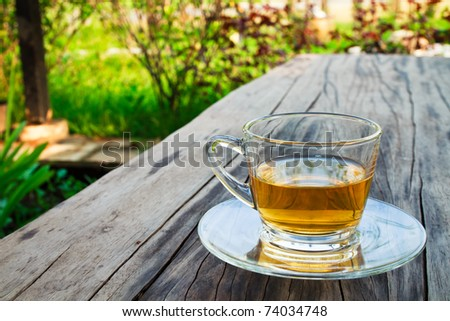 Cup of tea on the wooden table in the garden