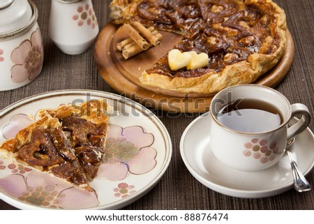 cup of tea or coffee and a romantic heart shaped and sliced apple pie