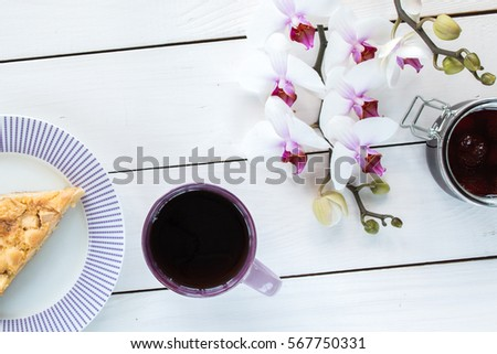 cup of tea or coffee, pie on the violet plate,  orchid flower, jar with strawberry jam on white colored wooden table,  top view #567750331