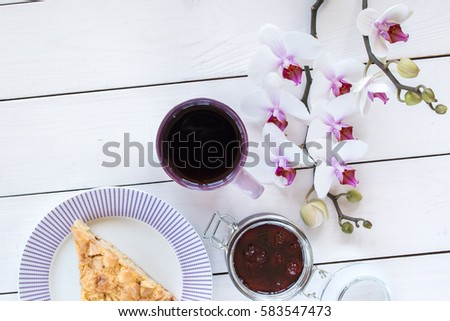 cup of tea or coffee, pie on the violet plate,  orchid flower, jar with strawberry jam on white colored wooden table,  top view #583547473