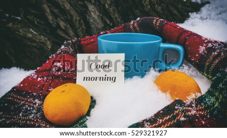 Cup of tea, red scarf and tangerines, words on paper good morning