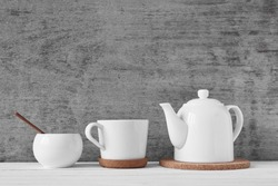 Cup of tea, teapot and sugar bowl on gray background