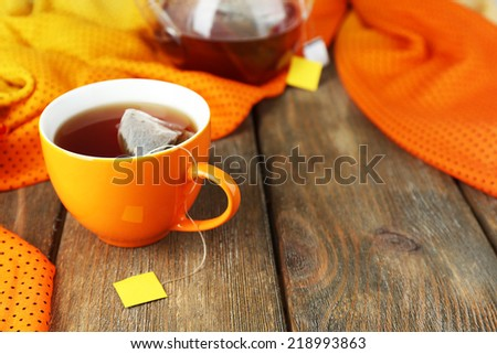 Cup of tea, teapot and tea bags on wooden table close-up #218993863