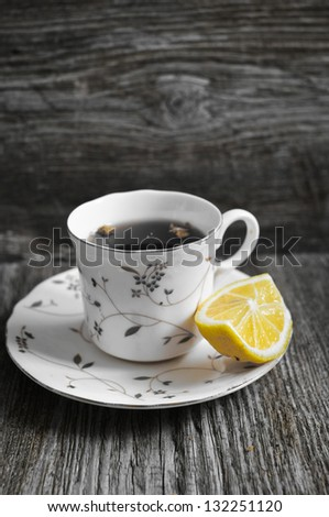 Cup of tea with a lemon on a wooden background