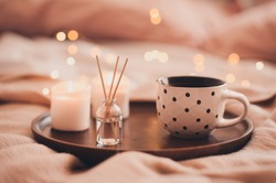 Cup of tea with aroma sticks and burning candles in bed staying on wooden tray closeup. Good morning. Winter holiday season. Cozy atmosphere.