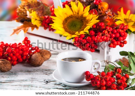 Cup of tea with autumn leaves with season vegetable on wooden table