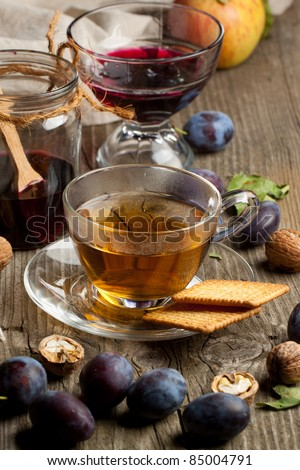 Cup of tea with berry jam and fresh fruits on old wooden table