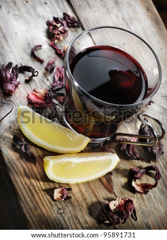 Cup of tea with dried hibiscus and lemon slices