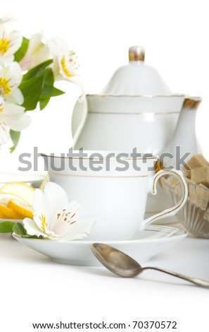 Cup of tea with flower.Teaset on table isolated over white