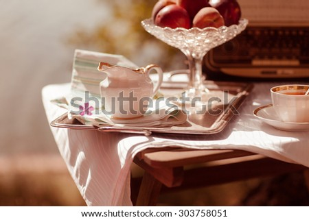 Cup of tea with flowers on table in autumn with fresh flower and towel on table