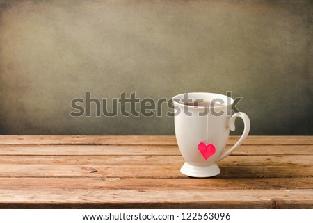 Cup of tea with heart shape on wooden table