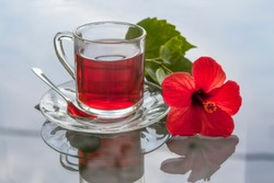 cup of tea with ibiscus flowers on a glass table