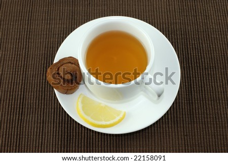 Cup of Tea with Lemon and Cake Pieces Isolated on Brown Tablecloth