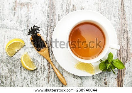 Cup of tea with lemon and mint on wooden background