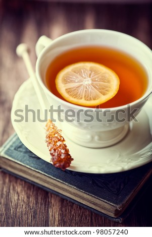 Cup of Tea with Lemon and Sugar Stick on a Old Book