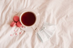 Cup of tea with macaron cookies and meds in bed with medical mask in bed closeup. Good morning. Quarantine at home time. Virus concept. Top view. Social isolation.