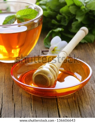 cup of tea with mint and honey on a wooden table