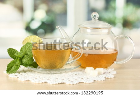 Cup of tea with mint and lime on table in room