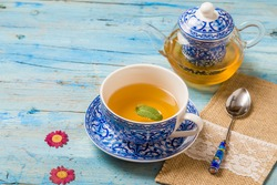 Cup of tea with mint leaf and transparent teapot on vintage blue wooden table