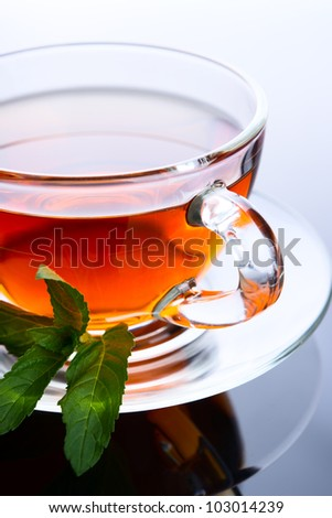 Cup of tea with mint leaf on a saucer