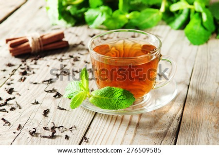 cup of tea with mint leaves on a wooden table