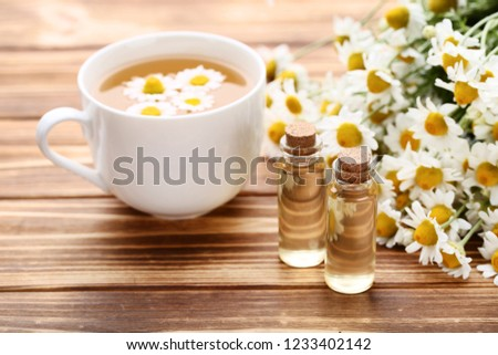 Cup of tea with oil in bottles and chamomile flowers on wooden table