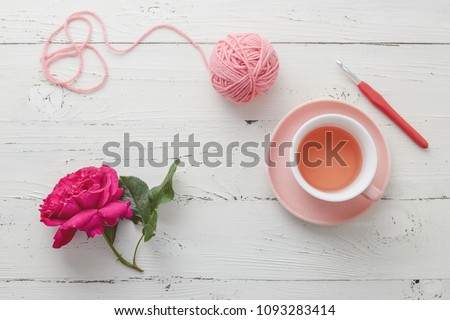 Cup of tea with pink ball of yarn, crochet hook and rose on white background.