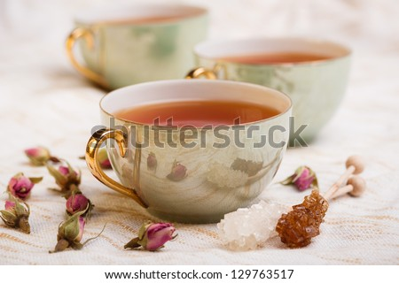 Cup of tea with rose bud and rock sugar sticks