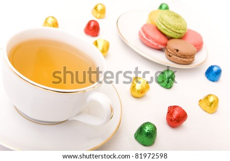 Cup of tea with some colorful chocolates and macaron