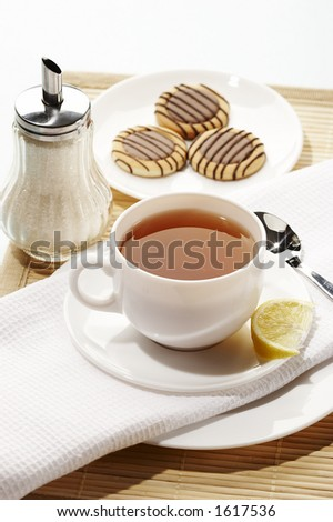 cup of tea with sugar bowl and some chocolate cookies