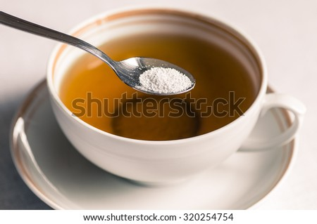 Cup of tea with sweetener sorbitol in a spoon
